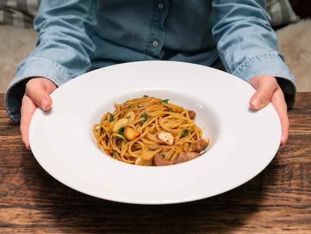Una femmina usa le mani per tenere e consegnare un piatto di spaghetti piccanti con salsiccia di maiale e aglio in una ciotola bianca, cucina italiana
