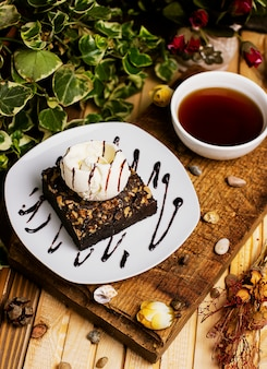 Una fetta di biscotto al cioccolato con gelato alla vaniglia e noci.