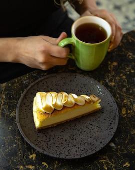 Una fetta di cheesecake condita con crema di meringa bruciata