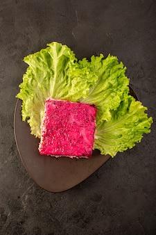 Una fetta di insalata di barbabietole vista dall'alto di insalata di maionese con piatto marrone interno verde sul buio