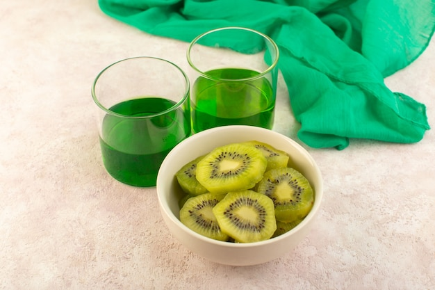 Una fetta di kiwi fresca vista frontale con succo di kiwi verde sulla bevanda di colore esotico frutta rosa scrivania