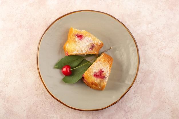 Una fetta di torta di ciliegie con vista dall'alto all'interno del piatto sullo zucchero rosa biscotto torta da scrivania dolce