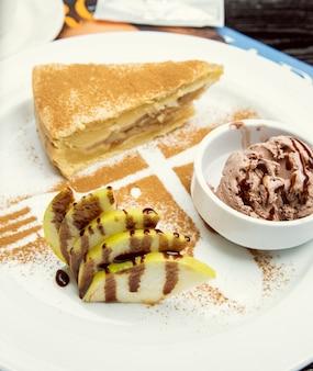 Una fetta di torta di mele con gelato al cioccolato, cannella in alto.