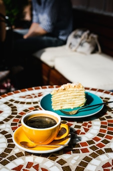 Una fetta di torta napoleone su un piatto blu e una tazza gialla di caffè nero in una giornata di sole su una terrazza di un caffè