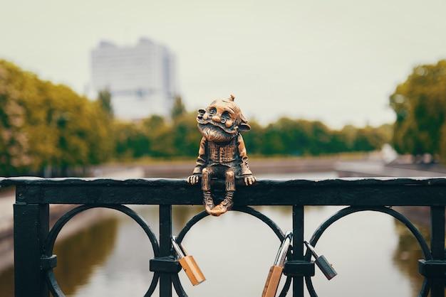 Una figura di bronzo, il vecchio homlin, siede sulla ringhiera del ponte.