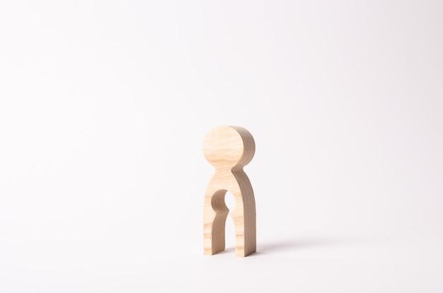 Una figura di legno di una donna con un vuoto dentro a forma di bambino.
