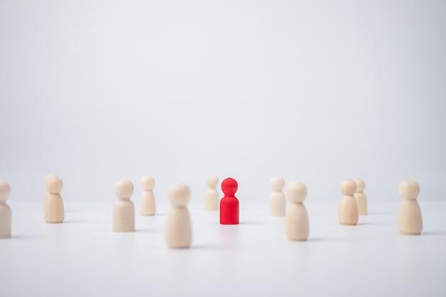 Una figura di legno in piedi con la squadra per influenzare e responsabilizzare.