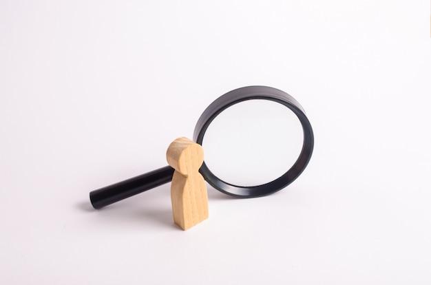 Una figura umana in legno si trova vicino a una lente di ingrandimento su uno sfondo bianco