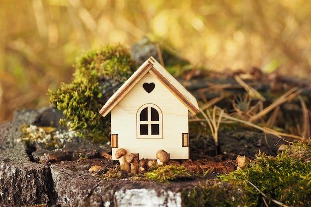 Una figurina in miniatura di una casa di legno su un ceppo di betulla con muschio e piccoli funghi.