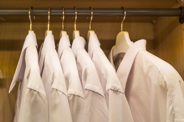 Una fila di camicie da uomo bianche simmetricamente appese