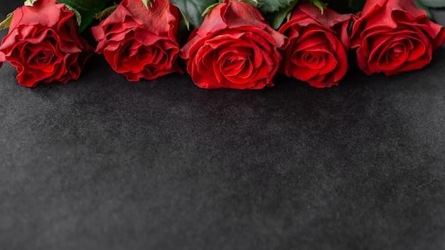 Una fila di cinque rose rosse sulla cartolina nera della parete con lo spazio della copia