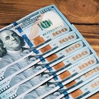 Una fila di contanti cento banconote americane su uno sfondo di legno