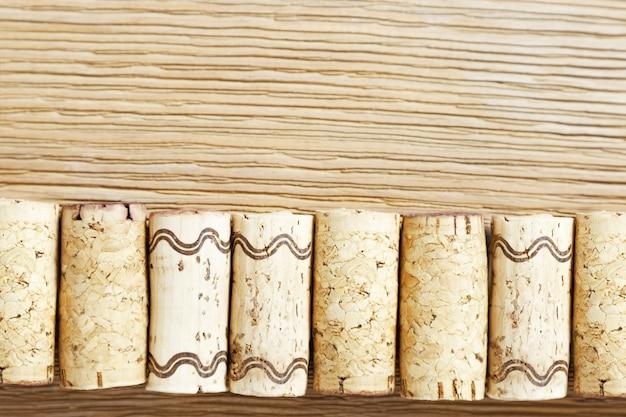 Una fila di tappi per vino usati su un vecchio tavolo di legno.