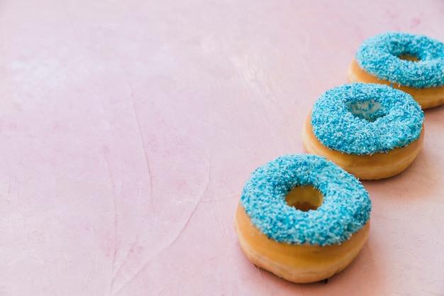 Una fila di tre ciambelle blu in una fila su fondo rosa