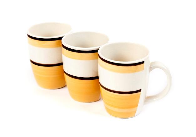 Una fila di tre tazze isolate su fondo bianco