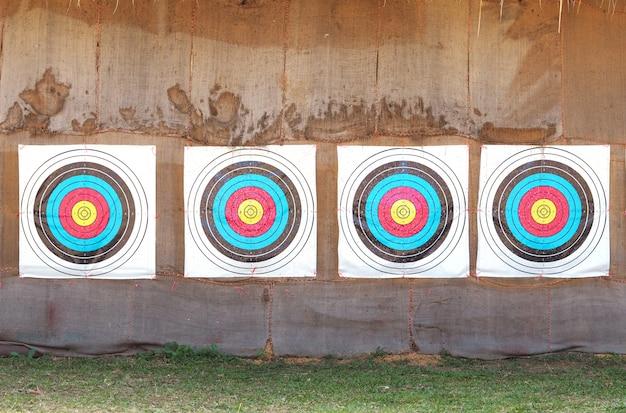 Una fila di un bersaglio di tiro con l'arco di quattro anelli su vecchio fondo marrone del tessuto.