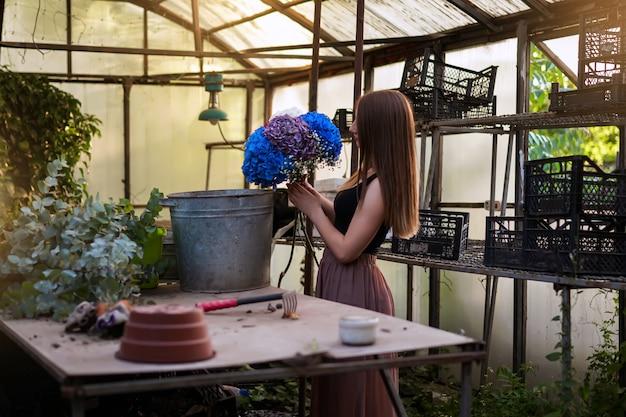 Una fioraia prepara un mazzo di ortensie in un bellissimo giardino
