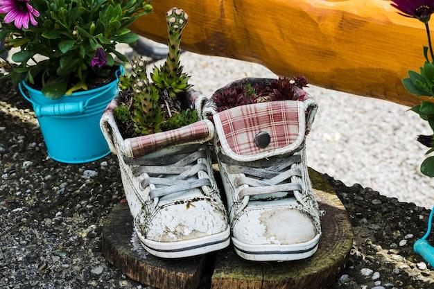 Una fioriera di pantofole vecchie e usate con fiori