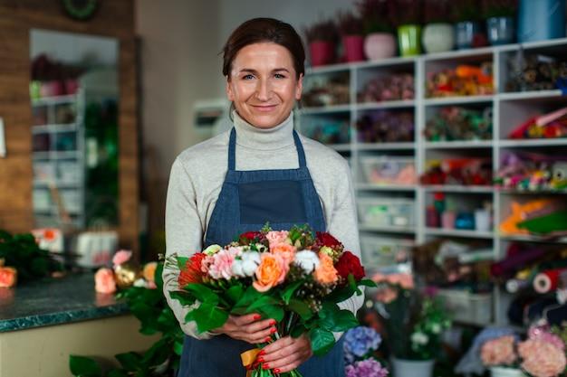 Una fiorista donna di buon carattere si trova nel mezzo di un negozio di fiori con un mazzo di splendidi fiori