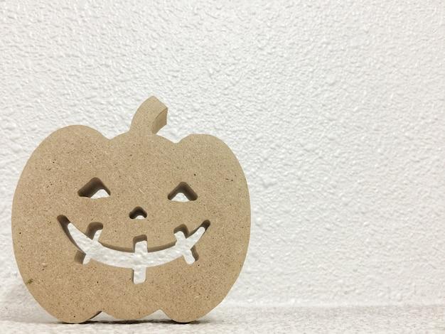 Una forma della zucca del fantasma di sorriso della carta marrone sul fondo bianco della parete dello spazio della copia del cemento.