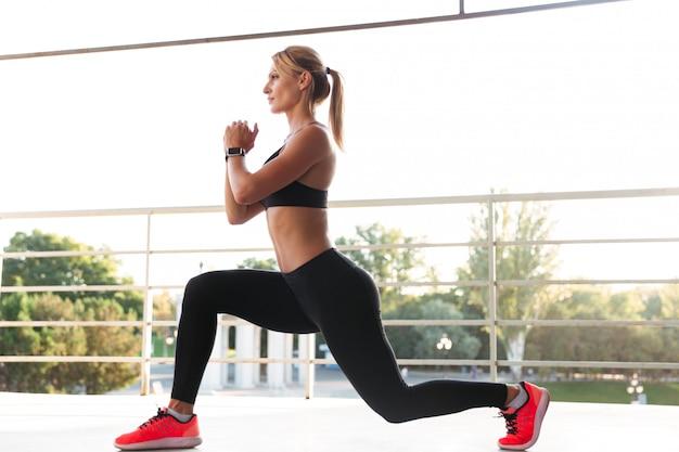 Una forte giovane donna sportiva fa esercizi sportivi.