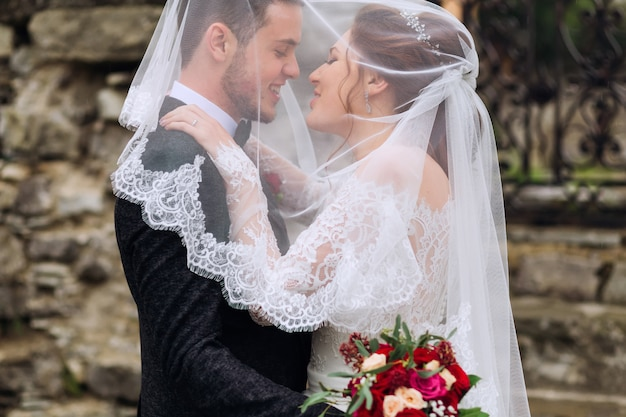 Una foto delicata degli sposi coperti da un velo da sposa sullo sfondo di un muro di pietra
