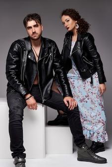 Una foto della bella coppia in giacche di pelle. abiti casual collezione uomo e donna. , muro grigio.