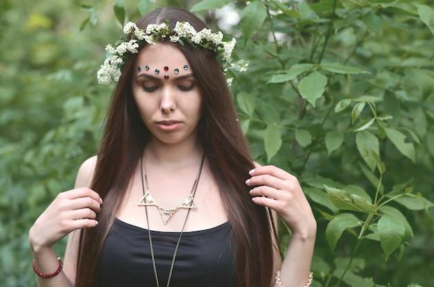 Una foto della foresta di una bella giovane bruna dall'aspetto europeo con occhi marrone scuro e labbra grandi. sulla testa della ragazza indossa una ghirlanda floreale, sulla fronte decorazioni luccicanti