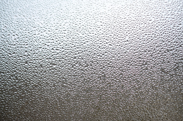 Una foto della superficie di vetro della finestra, coperta da una moltitudine di goccioline di varie dimensioni. texture di sfondo di uno strato denso di condensa su vetro