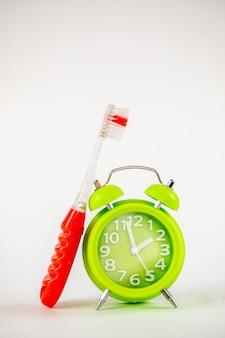 Una foto della sveglia e dello spazzolino da denti verdi. è ora di pulire i denti. cura dentale, foto di concetto di igiene personale. un promemoria importante per i bambini e gli adulti che si prendono cura dei loro denti.