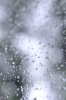 Una foto di pioggia scende sul vetro della finestra con una vista offuscata