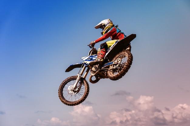 Una foto di un motociclista che fa una prodezza e salta in aria