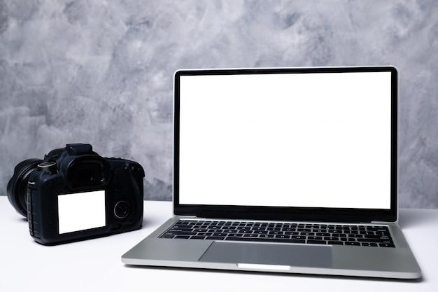 Una fotocamera digitale nera e un computer portatile su un tavolo.