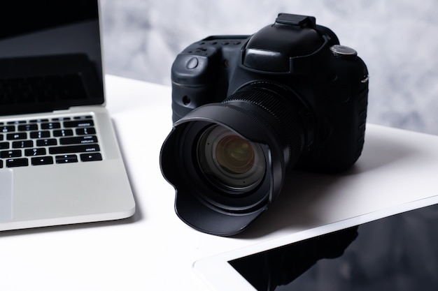 Una fotocamera digitale nera, un tablet e un computer portatile su un tavolo.
