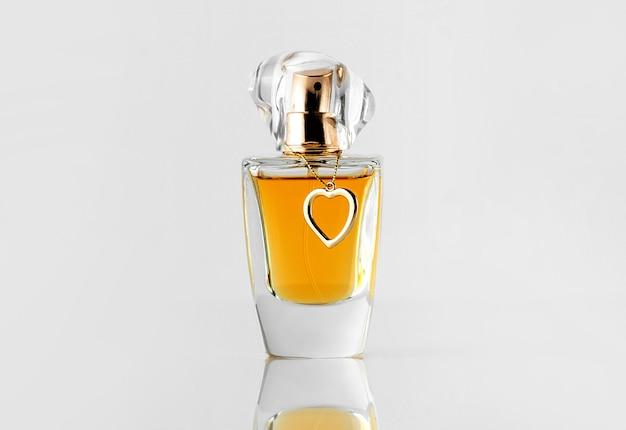 Una fragranza di bottiglia d'argento vista frontale con tappo dorato e linea gialla sul muro bianco