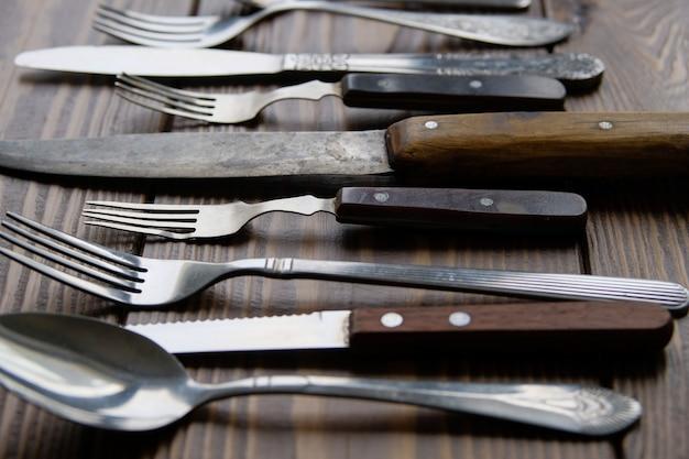Una gamma di diverse posate vintage con coltelli, forchette e cucchiai