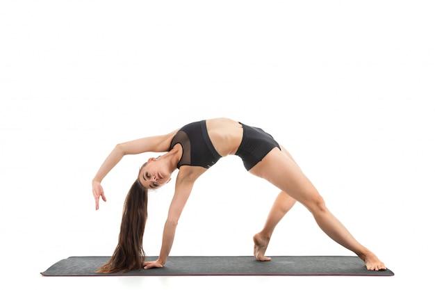 Una ginnasta giovane e bella con i capelli lunghi scuri riscalda e allunga i suoi muscoli.