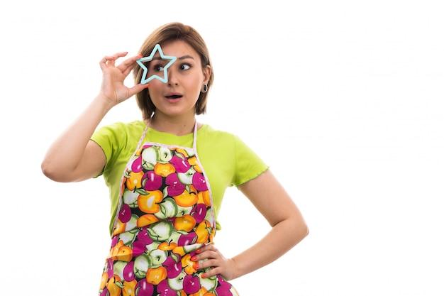 Una giovane bella casalinga di vista frontale in mantello variopinto della camicia verde che tiene la figura a forma di stella blu sulla cucina bianca di pulizia della casa del fondo