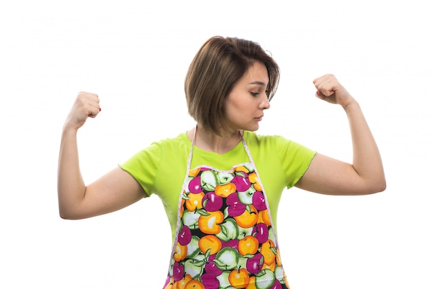 Una giovane bella casalinga di vista frontale nel mantello variopinto della camicia verde che flette forte sulla cucina bianca della femmina della casa del fondo