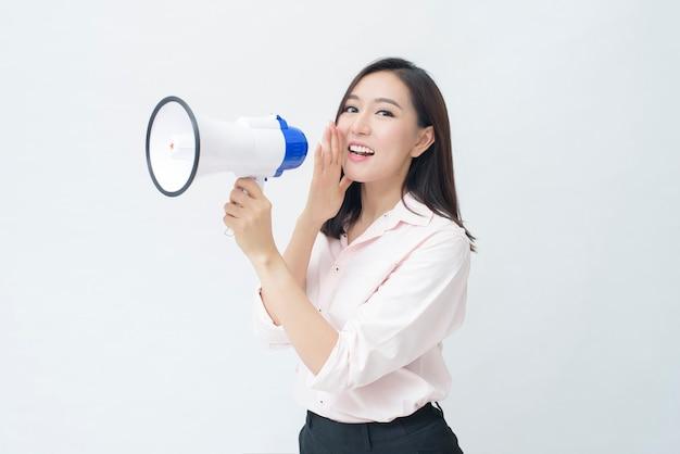 Una giovane bella donna asiatica sta annunciando dal megafono su sfondo bianco
