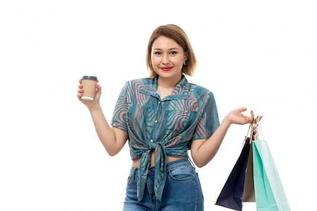 Una giovane bella donna di vista frontale in blue jeans colorati della blusa che tengono i caffè sorridenti della tenuta dei pacchetti di acquisto