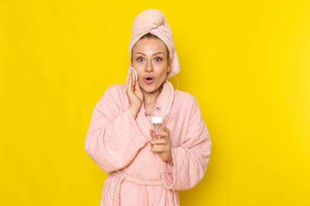 Una giovane bella femmina di vista frontale in accappatoio rosa che pulisce tutto il trucco con il pulitore