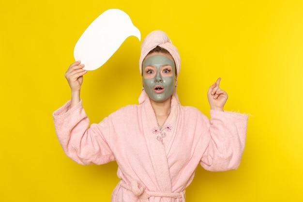 Una giovane bella femmina di vista frontale in accappatoio rosa che tiene segno bianco