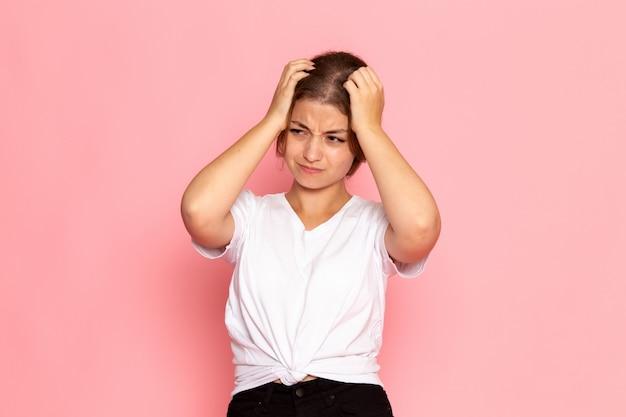 Una giovane bella femmina di vista frontale in camicia bianca che posa con l'espressione rattristata