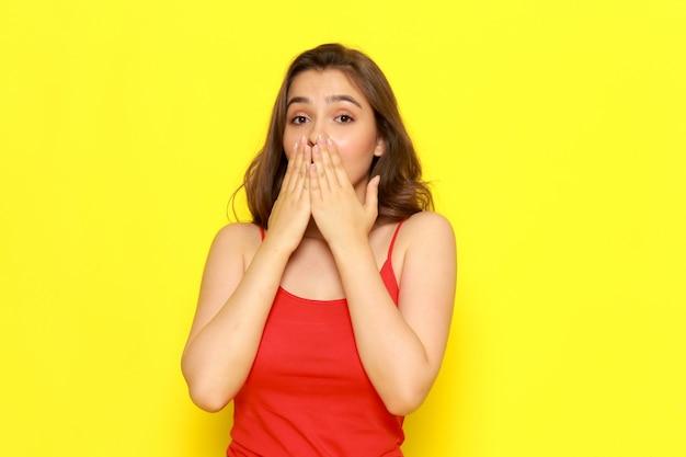 Una giovane bella ragazza di vista frontale in camicia e blue jeans rosse che posano con l'espressione colpita