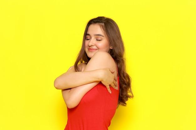 Una giovane bella ragazza di vista frontale in camicia rossa e blue jeans che si abbracciano