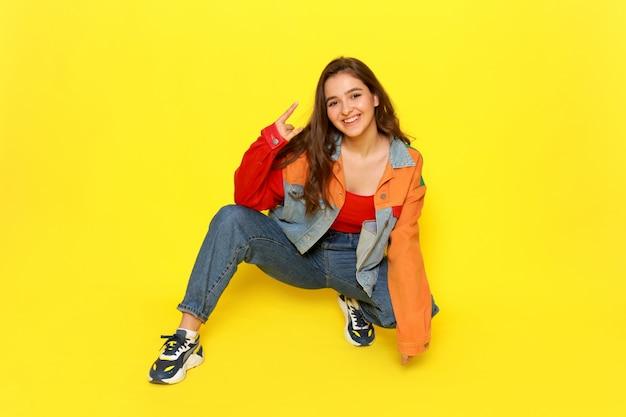 Una giovane bella ragazza di vista frontale in cappotto e blue jeans rossi della camicia che posano con l'espressione sorridente