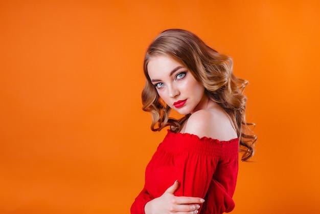 Una giovane bella ragazza mostra emozioni e sorrisi in studio su uno sfondo arancione. ragazze per la pubblicità.