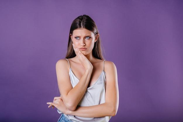 Una giovane bella ragazza mostra emozioni e sorrisi in studio su uno sfondo viola. ragazze per la pubblicità.