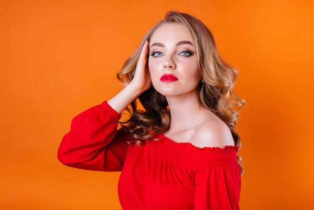 Una giovane bella ragazza mostra emozioni e sorrisi su uno spazio arancione. ragazze per la pubblicità.